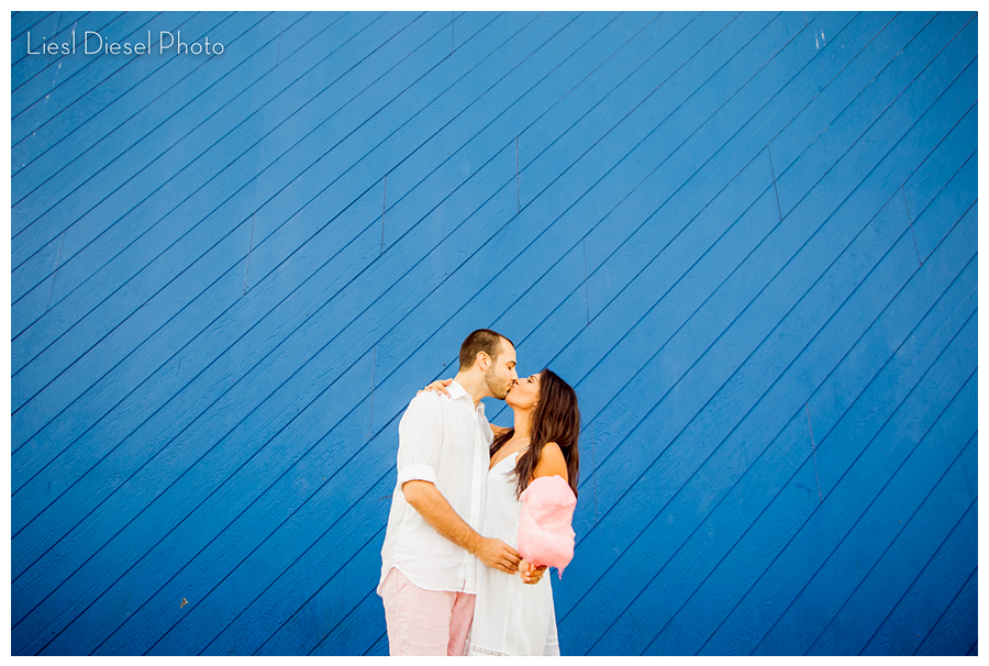 liesl diesel photo santa monica pier romantic engagement session cute whimsical cotton candy blue wall kiss